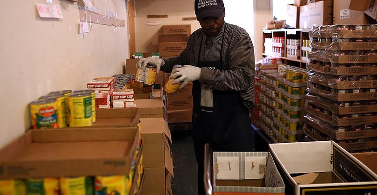 warehouse employee loads canned food into boxes