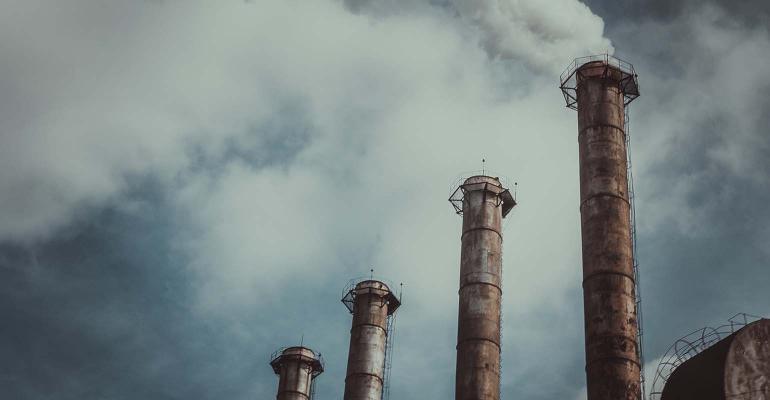 Smokestacks sending steam, pollution into atmosphere.