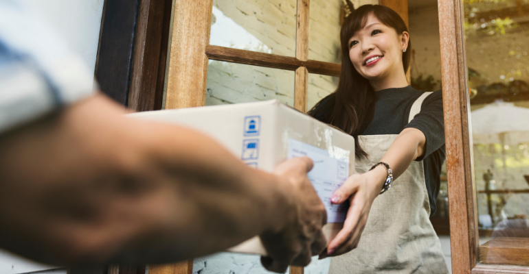 Woman delivering box at front door
