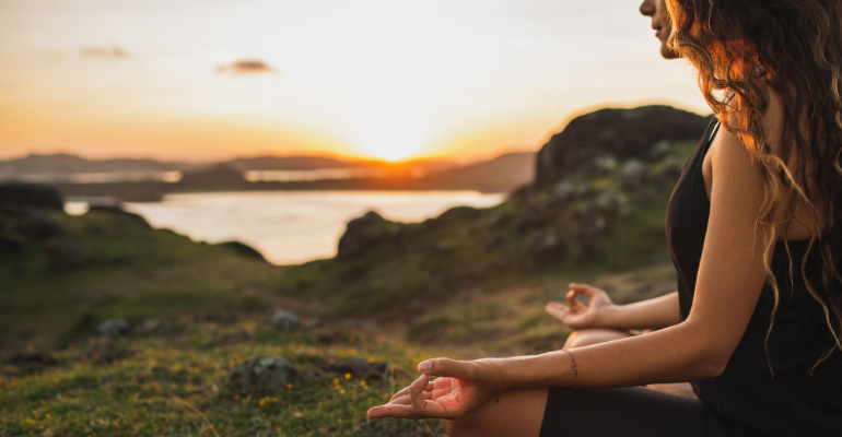 Person Meditating Outside at Sunset