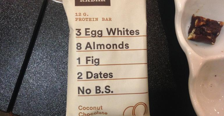 A simple bar with almost all of the ingredients printed on the front of the package RXBAR is a chocolatey coconuty and paleoperfect snack that contains 12 grams protein and sweetened just with dates and figs