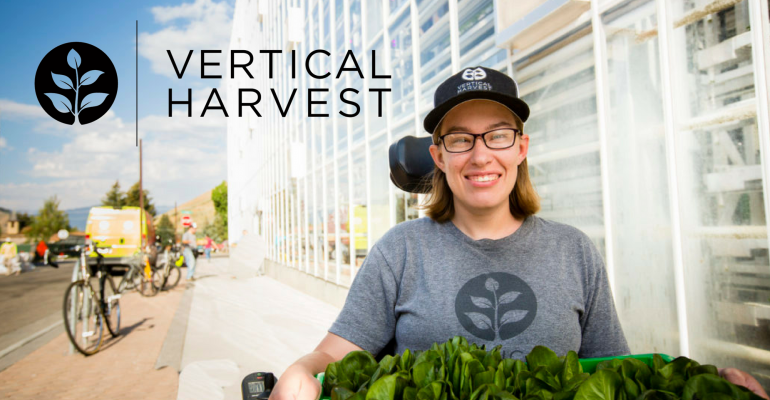 Vertical Harvest employee in front of building with greens