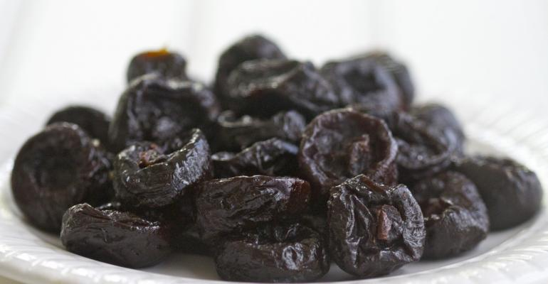 Dried plums on white plate