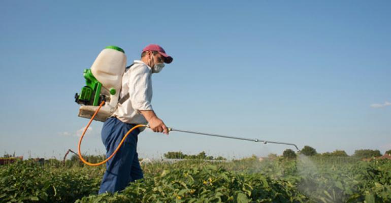 farmer spraying pesticides