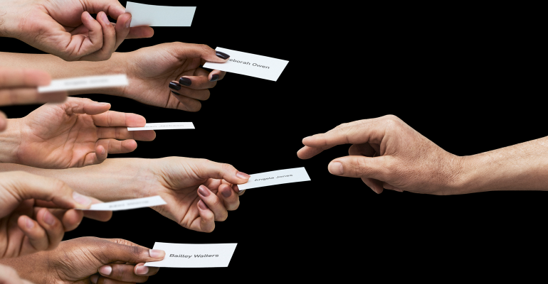 Hands holding papers with names