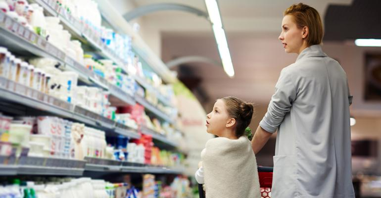 millennial mom grocery shopping with daughter