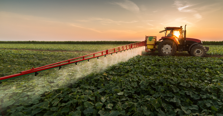 Tractor spraying pesticides on crops