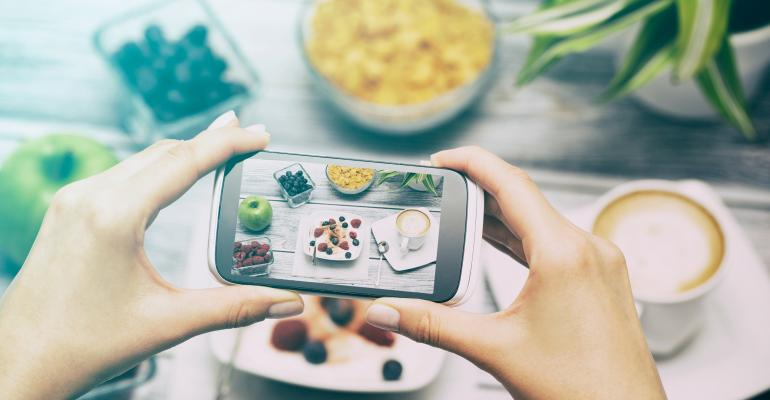 Person taking a picture of food with their smartphone