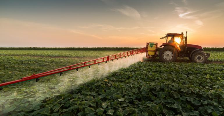 farmer spraying pesticides on field