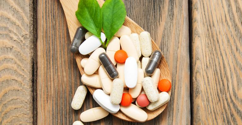supplements on wooden spoon