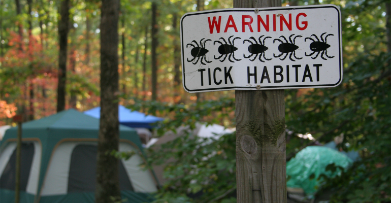 Camp site with tick habitat sign